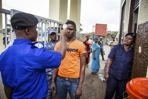 A health worker, left, uses a thermometer on a man outside the Youyi government buildings, part of measures to stem the spread of the Ebola virus, in Freetown, Sierra Leone  (AP Photo/Michael Duff, File)