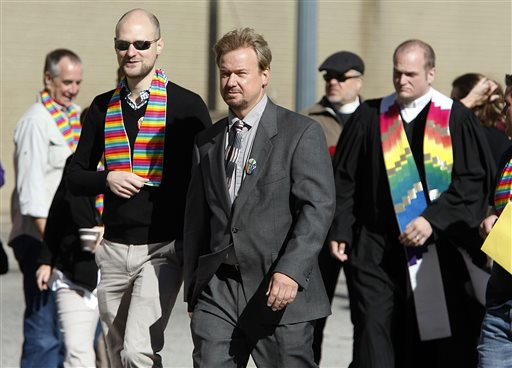Rev. Frank Schaefer, center, and his son, Tim Schaefer, second from left, walk to a meeting of the Judicial Council of the United Methodist Church, in Memphis (AP Photo/Karen Pulfer Focht)