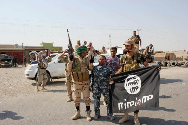 Shiite militiamen hold the flag of the Islamic State group they captured, during an operation outside Amirli, some 105 miles (170 kilometers) north of Baghdad (AP)