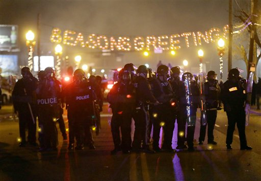 Police gather on the street as protesters react after the announcement of the grand jury decision Monday (AP Photo/Charlie Riedel)