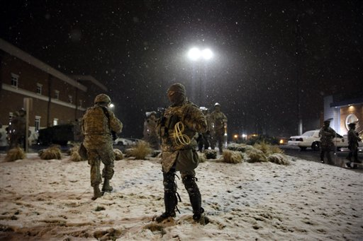 Snow falls as Missouri National Guard stand outside of the Ferguson Police Department Wednesday (AP Photo/Jeff Roberson)