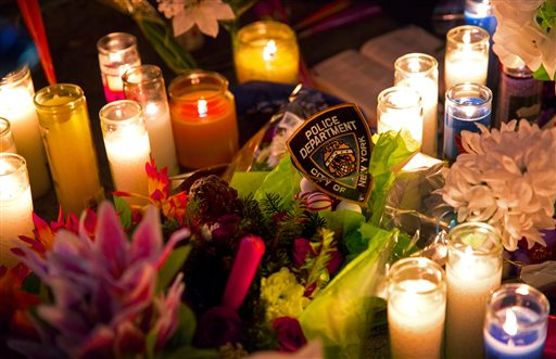 An NYPD arm patch rests with candles and flowers Sunday  (AP Photo/Craig Ruttle)