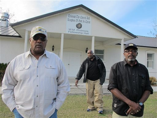 Alonzo Philmore, left, Harry Campbell, center, and Suwannee County NAACP president Leslie White stand in front of their church in Live Oak, Fla.  (AP Photo/Jason Dearen)