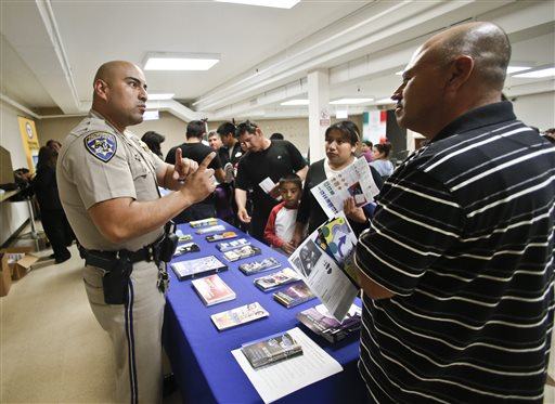 California Highway Patrol officer Armando Garcia explains to immigrants the process of getting a drivers license during an information session at the Mexican Consulate, in San Diego (AP Photo/Lenny Ignelzi)