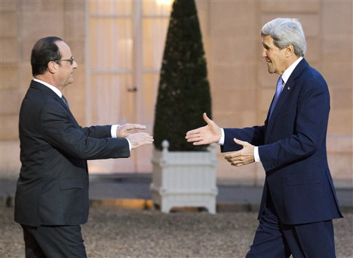 France's President Francois Hollande, left,  welcomes U.S. Secretary of State John Kerry, at the Elysee Palace in Paris  (AP Photo/Jacques Brinon)