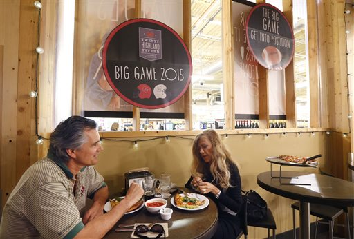 """So as not to infringe on the NFL Super Bowl name trademark, all non-rights holders have to use different wording to promote any Super Bowl activity like this Whole Foods grocery store where diners enjoy a meal near promotional signs for """"the big game"""" in Phoenix.  (AP Photo/Ross D. Franklin)"""