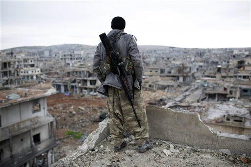 A Syrian Kurdish sniper looks at the rubble in the Syrian city of Ain al-Arab, also known as Kobani. (AP Photo)
