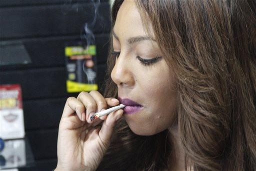 Alaska Cannabis Club CEO Charlo Greene smokes a joint at the medical marijuana dispensary in Anchorage, Alaska.  (AP Photo/Mark Thiessen)
