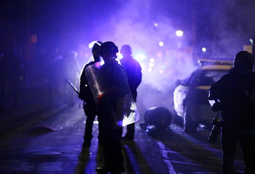 Police officers watch protesters as smoke fills the streets in Ferguson, Mo. after a grand jury's decision in the fatal shooting of Michael Brown. (AP Photo/Charlie Riedel)
