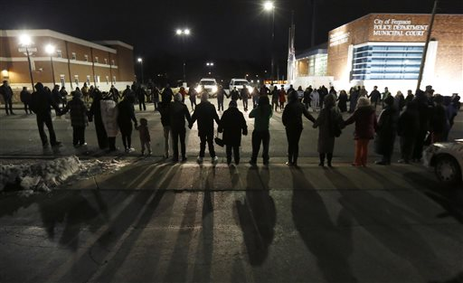 Protestors block traffic outside the Ferguson, Mo., police department.  (AP Photo/Charles Rex Arbogast)