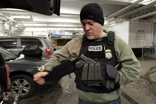 """An Immigration and Customs Enforcement officer """"tacs up"""" in the garage of a New York federal building, as he prepares for series of early-morning arrests.  (AP Photo/Richard Drew)"""