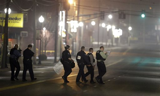 Police canvass the area as they investigate the scene where two police officers were shot outside the Ferguson Police Department Thursday in Ferguson, Mo.  (AP Photo/Jeff Roberson)