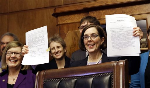 Oregon Gov. Kate Brown holds up an automatic voter registration bill after signing it.  (AP Photo/Don Ryan)