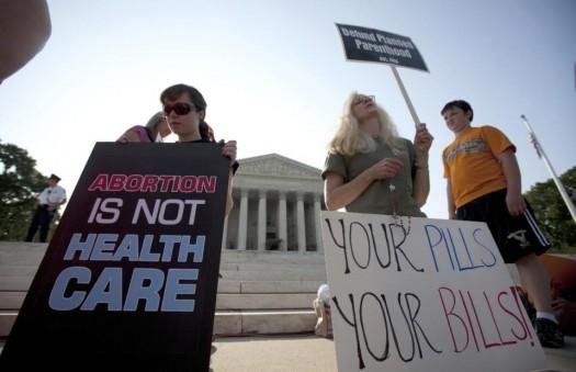 Demonstrators pray outside the Supreme Court in Washington before a landmark decision on health care.  (AP Photo/Evan Vucci)