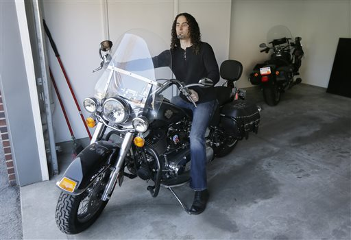 Eugene Gualtieri, a 41-year-old lab technician at the Detroit Medical Center, prepares to ride his motorcycle in Detroit.  (AP Photo/Carlos Osorio)