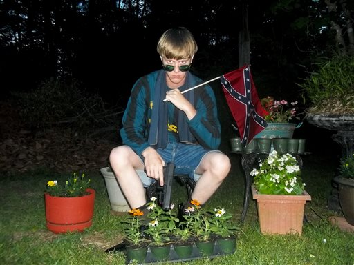 Lastrhodesian.com, a website being investigated by the FBI in connection with Charleston, S.C., shooting suspect Dylann Roof, shows Roof posing for a photo while holding a Confederate flag. The website surfaced online Saturday, June 20, 2015, and also contained a hate-filled 2,500-word essay that talks about white supremacy and concludes by saying the author alone will need to take action. (Lastrhodesian.com via AP)