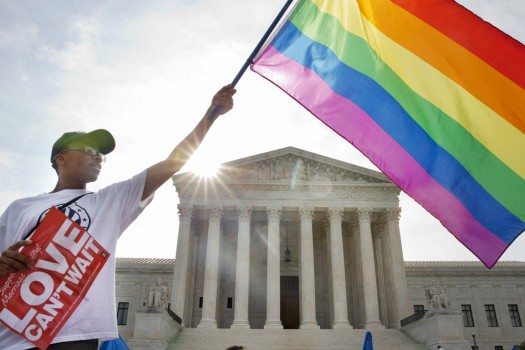 Carlos McKnight of Washington, waves a flag in support of gay marriage outside of the Supreme Court in Washington, Friday.  (AP Photo/Jacquelyn Martin)