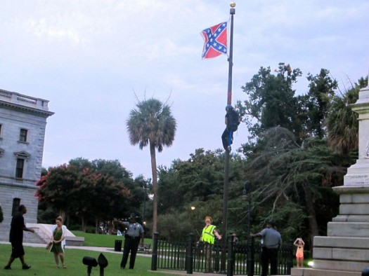 Police surround the flagpole flying the Confederate battle flag at a Confederate monument  at the Statehouse in Columbia, S.C., on Saturday as Bree Newsome of Charlotte, N.C. climbs the pole to remove the banner.  (AP Photo/Bruce Smith)