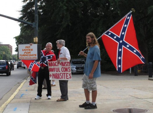 William Cheek, left, Nelson Waller, center, and Jim Collins, right, protest proposals to remove the Confederate flag from the grounds of the South Carolina Statehouse. (AP Photo/Jeffrey Collins)