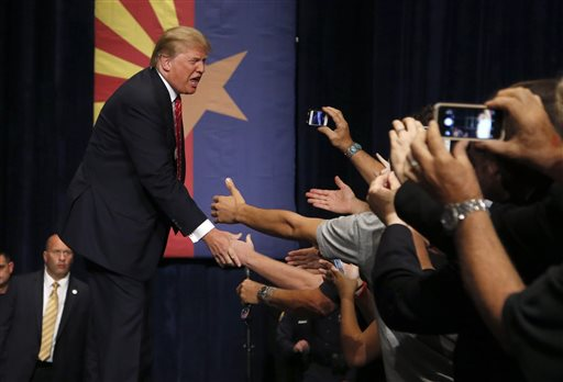 Republican presidential candidate Donald Trump shakes hands prior to speaking at a rally before a crowd of 3,500 , in Phoenix. (AP Photo/Ross D. Franklin)