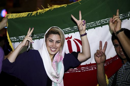 An Iranian woman shows the victory sign as people celebrate on a street following a landmark nuclear deal, in Tehran, Iran.  (AP Photo/Ebrahim Noroozi)