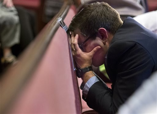 Chad Harris puts his face against a pew as he prays during a prayer vigil at Redemption Point Church for the victims of shootings at a recruiting center and another U.S. military site a few miles apart in Chattanooga, Tenn., (Doug Strickland/Chattanooga Times Free Press via AP)