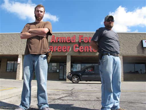 Allen Bowles, left, and Clint Janney stand guard outside a military recruiting center in Columbus, Ohio. (AP Photo/Andrew Welsh-Huggins)