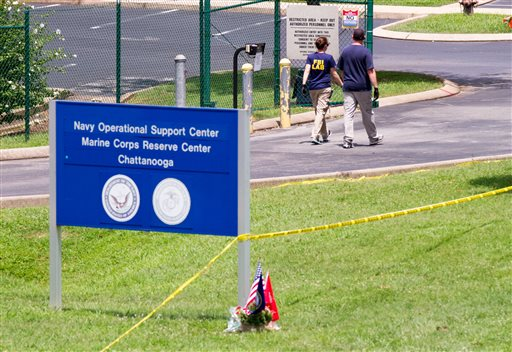 Investigators walk by the entrance of a Navy and Marine center in Chattanooga, Tenn. (AP Photo/Erik Schelzig)