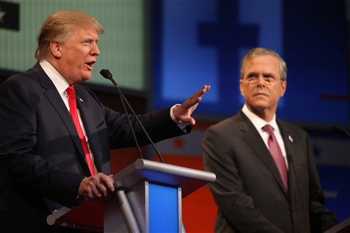 Republican presidential candidate Donald Trump, left, speaks as Jeb Bush listens during the first Republican presidential debate at the Quicken Loans Arena Thursday, Aug. 6, 2015, in Cleveland. (AP Photo/Andrew Harnik)