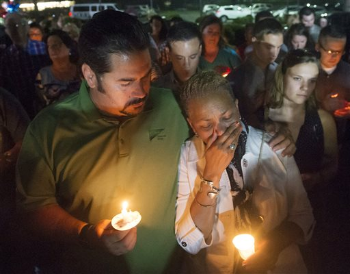Roanoke City Council member Anita Price, right, is comforted by friend Jan DeVries as they gather at a candlelight vigil in front of the WDBJ-TV station in Roanoke, Va., Thursday, Aug. 27, 2015, a day after reporter Alison Parker and cameraman Adam Ward from the station were killed during a live broadcast. Vester Flanagan filmed himself gunning down the journalists and posted the video on social media after fleeing the scene. (AP Photo/Don Petersen)