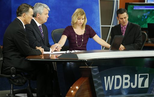 WDBJ-TV7 news morning anchor Kimberly McBroom, second from right, and meteorologist Leo Hirsbrunner, right, are joined by visiting anchor Steve Grant, second from left, and Dr. Thomas Milam, of the Carilion Clinic, as they observe a moment of silence during the early morning newscast at the station, in Roanoke, Va., Thursday, Aug. 27, 2015. The moment of silence was at the moment reporter Alison Parker and cameraman Adam Ward were killed during a live broadcast Wednesday, while on assignment in Moneta. (AP Photo/Steve Helber)