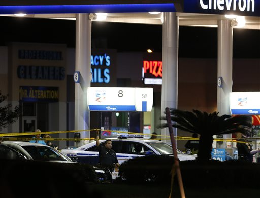 Officials investigate the scene at a gas station where a sheriff's deputy in uniform was fatally shot Friday, Aug. 28, 2015, in Houston. Harris County Sheriff's Office spokesman Ryan Sullivan said the deputy was pumping gas into his vehicle on Friday night when a man approached him from behind and fired multiple shots. (Karen Warren/Houston Chronicle via AP) MANDATORY CREDIT