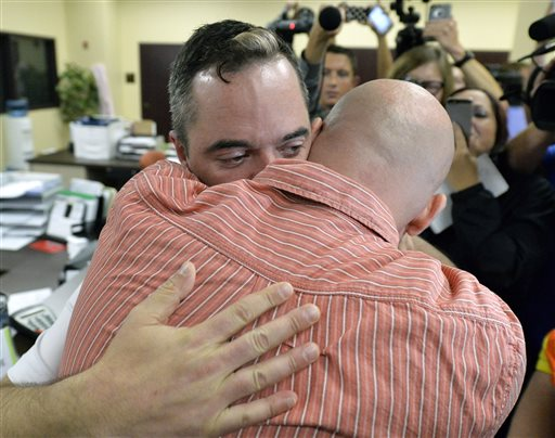 James Yates, left, hugs his partner William Smith Jr., after receiving their marriage license at the Rowan County Judicial Center in Morehead, Ky., Friday, Sept. 4, 2015.  Deputy clerk Brian Mason issued the license, congratulating the couple and shaking their hands as he smiled. (AP Photo/Timothy D. Easley)