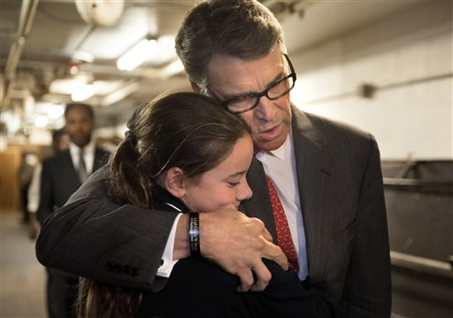 Republican presidential candidate, former Texas Gov. Rick Perry embraces Madeline Martin, daughter of Eagle Forum president Ed Mark, before speaking at the Eagle Council XLIV, sponsored by the Eagle Forum in St. Louis Friday, Sept. 11, 2015. During the speech Perry said he is ending his second bid for the Republican presidential nomination, becoming the first major candidate of the 2016 campaign to give up on the White House.  (AP Photo/Sid Hastings)