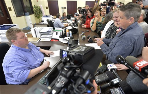 Rowan County Deputy Clerk Brian Mason, left, asks Shannon Wampler-Collins, right and her partner Carmen Wampler-Collins to double check their marriage license at the Rowan County Judicial Center in Morehead, Ky. Monday, Sept. 14, 2015. Rowan County Clerk Kim Davis announced earlier that her office will issue marriage licenses under order of a federal judge, but will not have her name or office listed. (AP Photo/Timothy D. Easley)