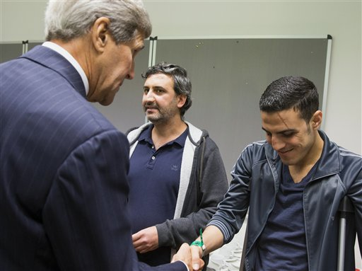 US Secretary of State John Kerry, left, talks with a man injured in a bomb attack in Syria during a meeting with a group of refugees fleeing Syria, at Villa Borsig, Sunday, Sept. 20, 2015, in Berlin. (AP Photo/Evan Vucci, Pool)