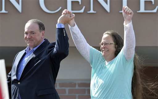 FILE - In this Sept. 8, 2015, file photo, Rowan County Clerk Kim Davis, with Republican presidential candidate Mike Huckabee at her side, greets the crowd after being released from the Carter County Detention Center, in Grayson, Ky. Davis, hauled to jail for defying a series of federal court orders and refusing to issue marriage licenses to same-sex couples, filed a 40-page court document Thursday, Sept. 24, blaming Kentucky governor Steve Beshear for all her legal woes. (AP Photo/Timothy D. Easley, File)
