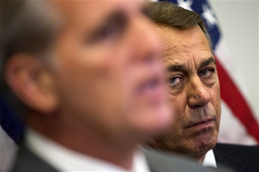 In this Oct. 7, 2015, photo, outgoing House Speaker John Boehner of Ohio listens at right as House Majority Leader Kevin McCarthy of Calif., speaks during a new conference on Capitol Hill in Washington. Boehner wants out. He really does. But the Ohio House Republican is staying put, for now _ and that could improve the chances for a debt limit increase by early next month to avoid a market-shattering government default and possibly a bipartisan budget deal to head off a government shutdown in December. Conservative hardliners have already forced Boehner to announce he's leaving and then caused further chaos by blocking the ascension of McCarthy. (AP Photo/Evan Vucci)