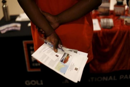 A job seeker holds literature while waiting to speak with a representative of the Golden Gate National Parks Conservancy at a career fair in San Francisco, California July 14, 2015. REUTERS/Robert Galbraith