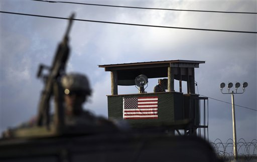 FILE - In this March 30, 2010 file photo, reviewed by the U.S. military, a U.S. trooper mans a machine gun in the turret on a vehicle as a guard looks out from a tower in front of the detention facility at Guantanamo Bay U.S. Naval Base, Cuba.  The Pentagon is expected to roll out a plan next week outlining its long-stalled effort to close the Guantanamo Bay detention center, and will include details suggesting the Centennial Correctional Facility in Colorado is a more suitable site to send detainees that officials believe should never be released.  (AP Photo/Brennan Linsley, File)
