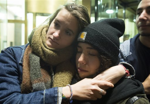 """People attend a vigil outside the French consulate in Montreal, Friday, Nov. 13, 2015. Canadian Prime Minister Justin Trudeau offered """"all of Canada's support"""" to France on Friday night in the wake of """"deeply worrying"""" terrorist attacks in Paris. (Graham Hughes/The Canadian Press via AP)"""