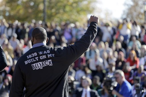 FILE - In this Nov. 9, 2015, file photo, a member of the black student protest group Concerned Student 1950 gestures while addressing a crowd following the announcement that University of Missouri System President Tim Wolfe would resign, at the university in Columbia, Mo. The bullet points are blunt and direct: Blacks at the University of Missouri are harassed and threatened, the university has too few African-American faculty members, administration doesn't seem to care, and all of that needs to change. A set of demands addressing those concerns is strikingly similar to demands made in 1969. But this time, it appears the university is listening. (AP Photo/Jeff Roberson, File)