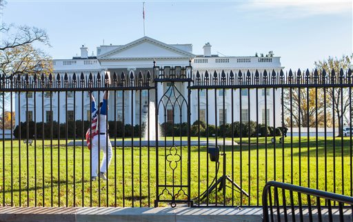 In this photo provided by Vanessa Pena, a man gestures after jumping a fence at the White House on Thursday, Nov. 26, 2015, in Washington. The man was immediately apprehended and taken into custody pending criminal charges, the Secret Service said. President Barack Obama and his wife and daughters were spending Thanksgiving the holiday at the White House. (Vanessa Pena via AP) MANDATORY CREDIT