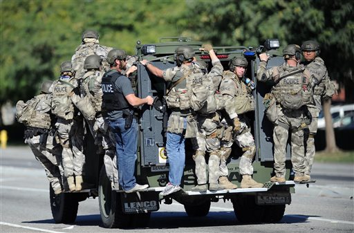 A SWAT vehicle carries police officers near the scene of a shooting in San Bernardino, Calif. on Wednesday, Dec. 2, 2015. Police responded to reports of an active shooter at a social services facility.   (Micah Escamilla/Los Angeles News Group via AP)
