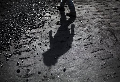 Superintendent Jackie Ratliff, a coal miner of 25 years, walks towards a pile of coal waiting to be shipped at a processing plant Tuesday, Oct. 6, 2015, in Welch, W.Va. Central Appalachia's struggle is familiar to many rural regions across the U.S., where middle-class jobs are disappearing or gone and young people have no other choice than to leave to find opportunity. But the problems are amplified in coal country, where these difficult economic and social conditions have gripped the region for decades and where there is hardly any flat land to build anything. (AP Photo/David Goldman)