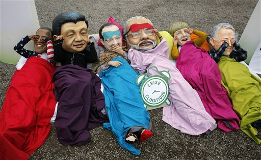 Oxfam activists wear masks of from left, U.S. President Barack Obama, Chinese President Xi Jinping,  French President Francois Hollande, India's Prime Minister Narendra Modi, German Chancellor Angela Merkel and Australia's Prime Minister Malcolm Turnbull as they stage a protest during the COP21, United Nations Climate Change Conference in Le Bourget, north of Paris, Thursday, Dec. 10, 2015.  (AP Photo/Christophe Ena)