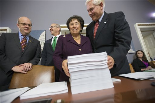 House Rules Committee Chairman Pete Sessions, R-Texas, right, welcomes Rep. Nita Lowey, D-N.Y., the ranking member of the House Appropriations Committee, and Rules Committee member Rep. James P. McGovern, D-Mass., far left, as they gather around a printout of the $1.1 trillion spending bill to fund the government for the 2016 budget year and extend $680 billion in tax cuts for businesses and individuals, at the Capitol in Washington, Wednesday, Dec. 16, 2015. President Barack Obama is expected to sign the legislation.  (AP Photo/J. Scott Applewhite)