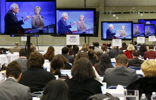 Bernie Sanders, left, speaks as Hillary Clinton listens during a Democratic presidential primary debate shown on TV screens in the media filing room, Saturday, Dec. 19, 2015, at Saint Anselm College in Manchester, N.H. (AP Photo/Michael Dwyer)