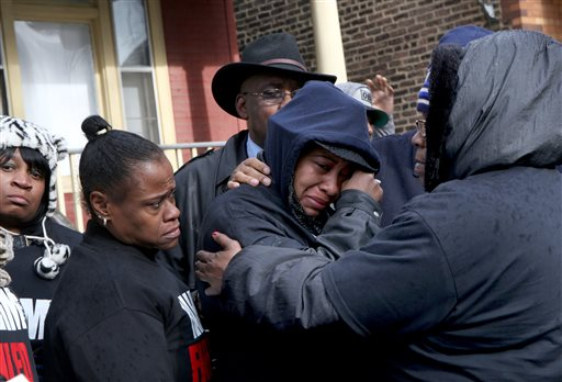 Janet Cooksey, center, the mother of Quintonio LeGrier, is comforted by family and friends during a press conference to speak out about Saturday's shooting death of her son by the Chicago police, on Sunday, Dec. 27, 2015, in Chicago. Grieving relatives and friends of two people shot and killed by Chicago police said Sunday that the city's law enforcement officers had failed its residents. (Nancy Stone/Chicago Tribune via AP) MANDATORY CREDIT