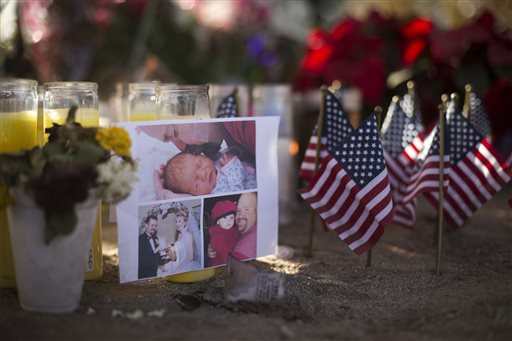 A photo collage of Robert Adams, one of the victims in the San Bernardino shootings at the Inland Regional Center, is placed next to small American flags at a makeshift memorial, Tuesday, Dec. 8, 2015, in San Bernardino, Calif. Just days before Syed Farook carried out the attack that killed multiple people, Farook practiced with a rifle during one of several recent visits to a local shooting range, authorities said. Sometimes he was joined by his wife, his partner in the attack. (AP Photo/Jae C. Hong)